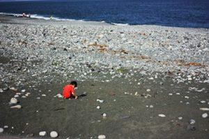 子供といっしょに浜辺でガラス片を拾う